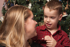 Adorable Son Talking to Mom in Front Of Christmas Tree royalty free stock image
