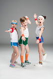 Adorable sporty kids in sportswear standing together and posing  on grey Stock Image