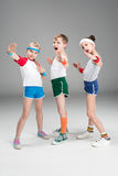 Adorable sporty kids in sportswear standing together and posing on grey. Children sport concept stock photos