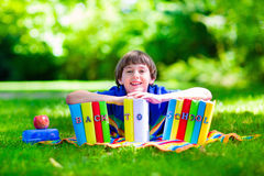 Adorable student boy relaxing in school yard reading books Stock Photos