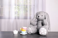 Adorable stuffed bunny and toy tableware on table, space for text. Child room elements. Adorable stuffed bunny and toy tableware on table indoors, space for text royalty free stock images