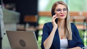 Adorable stylish businesswoman talking using smartphone having positive emotion at modern office. Background medium shot. Smiling fashion business female in stock footage
