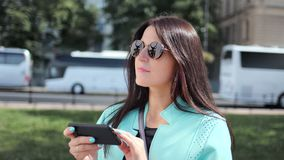 Adorable stylish female traveler using smartphone looking on electronic map at city background. Medium close-up. Smiling fashion tourist woman enjoying digital stock video footage