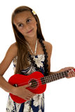 Adorable tan girl playing a red ukulele in a tropical dress Royalty Free Stock Images