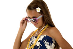 Adorable tan girl wearing a tropical dress playing with her glass royalty free stock photography