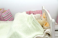An adorable teddy bear laying in bed, under the sheets Royalty Free Stock Image