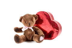 Adorable teddy bear next to heart Stock Images