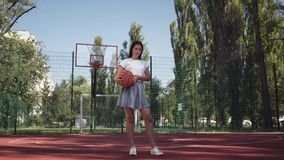 Adorable teen brunette girl holding a basketball ball looking at the camera standing on the basketball court outdoors. Concept of sport, power, competition stock video