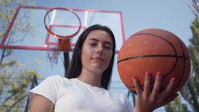 Portrait adorable teen brunette girl holding a basketball ball looking at the camera standing on the basketball court. Adorable teen brunette girl holding a stock video footage