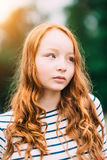 An adorable teenage girl with long curly ginger hair Stock Photography