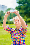 Adorable teenage girl taking picture with smartphone on sunny day. Adorable teenage girl taking picture with smartphone in sunny day in summer park. Teenage girl royalty free stock photography