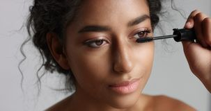 Adorable teenage Middle Eastern girl with great skin applying mascara to her long lashes Stock Photos