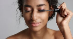 Adorable teenage Middle Eastern girl with great skin applying mascara to her long lashes. On white background Stock Photography