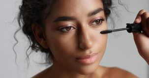 Adorable teenage Middle Eastern girl with great skin applying mascara to her long lashes Royalty Free Stock Photos