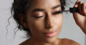 Adorable teenage Middle Eastern girl with great skin applying mascara to her long lashes Royalty Free Stock Image