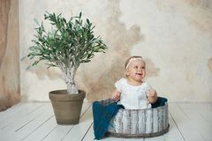 Adorable Ten month old newborn baby girl sitting in a wooden bucket. old baby in bedroom. father& x27;s day. father and daughter. Adorable Ten month old newborn royalty free stock photos