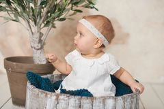 Adorable Ten month old newborn baby girl sitting in a wooden bucket. old baby in bedroom. father& x27;s day. father and daughter. Adorable Ten month old newborn royalty free stock image