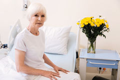 Adorable tender aged lady sitting in her hospital room Royalty Free Stock Images