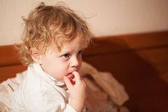 Adorable thoughtful little child. With curly blond hair sitting chewing a finger and staring ahead with a pensive expression watching cartoons on tv Stock Images