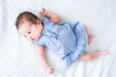 Adorable tiny newborn baby girl in a blue dress Stock Photo