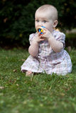 Adorable toddle on a lawn in a park. Close-up portrait of an adorable toddler sitting on a lawn in a park Royalty Free Stock Photos