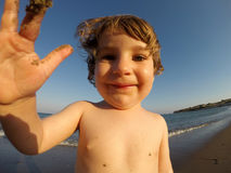 Adorable toddler baby playing with sand on a beach Royalty Free Stock Photos
