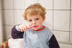 Adorable toddler with blue eyes and blond hair brushing his teet Stock Photo