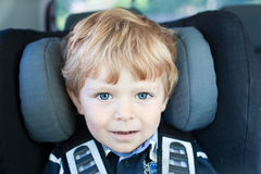 Adorable toddler with blue eyes in safety car seat Stock Images