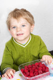 Adorable toddler boy with blond hairs eating fresh raspberries a Stock Images