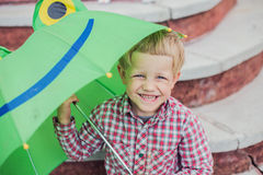 Adorable toddler boy with green frog umbrella Stock Image