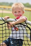 Adorable toddler boy hanging on a practice net Royalty Free Stock Photos