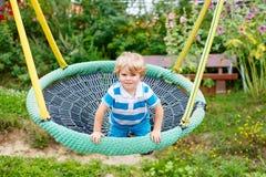 Adorable toddler boy having fun chain swing on outdoor playgroun Stock Photos