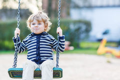 Adorable toddler boy having fun chain swing on outdoor playgroun Stock Images