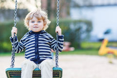 Adorable toddler boy having fun chain swing on outdoor playgroun Royalty Free Stock Photography