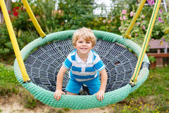 Adorable toddler boy having fun chain swing on outdoor playgroun Stock Photography