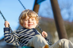 Adorable toddler boy having fun chain swing on outdoor playground. Little kid boy having fun and swinging on outdoor playground. Happy smiling child enjoying Royalty Free Stock Images