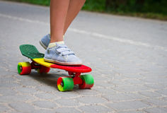 Adorable toddler boy having fun with colorful skateboard outdoors in the park Stock Image
