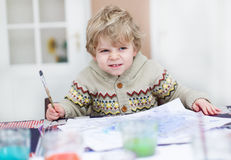 Adorable toddler boy having fun indoor, painting with different Stock Photos