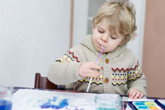 Adorable toddler boy having fun indoor, painting with different Royalty Free Stock Photo