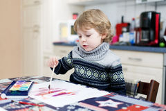Adorable toddler boy having fun indoor, painting with different Stock Photography