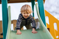 Adorable toddler boy having fun and sliding on outdoor playgroun Stock Image