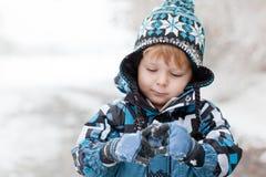 Adorable toddler boy having fun with snow Stock Photos