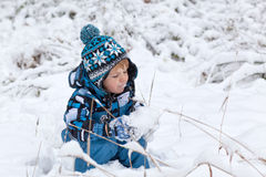 Adorable toddler boy having fun with snow Stock Photos
