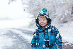 Adorable toddler boy having fun with snow on winter day Stock Images
