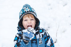 Adorable toddler boy having fun with snow on winter day Royalty Free Stock Images