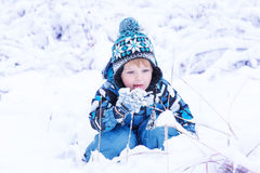 Adorable toddler boy having fun with snow on winter day Stock Photo