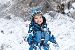 Adorable toddler boy having fun with snow on winter day Stock Image