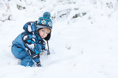 Adorable toddler boy having fun with snow on winter day Royalty Free Stock Photo
