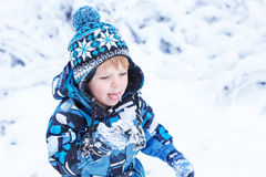 Adorable toddler boy having fun with snow on winter day Stock Photos