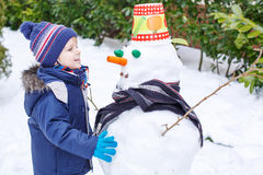 Adorable toddler boy having fun with snowman on winter day Stock Photography